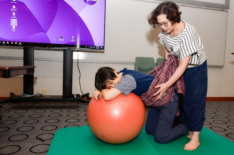 Lam Kit Yee demonstrating the way of using yoga ball & carrier for labour woman during the sharing